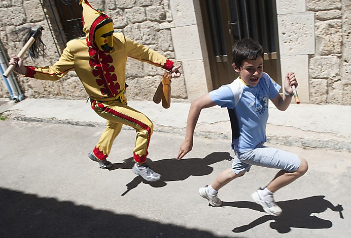 A man dressed in a red and yellow costume representing the devil runs through the streets chasing a boy during traditional Corpus Christi celebrations, in Castrillo de Murcia